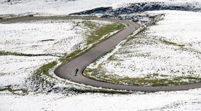 骑自行车者沿在一个多雪的风景的一条山路前进下坡 库存照片