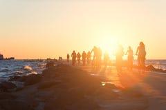 骑自行车者沿堤道乘坐到往太阳的海 库存照片