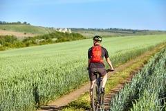 年轻骑自行车者的背面图有循环在领域的轨道的背包的 免版税图库摄影