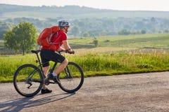 骑自行车者的Potrtrait一条漫长的路的在反对夏天风景的乡下 库存照片