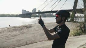 骑自行车者藏品为在小山的照相机电话河和城市身分照相 桥梁和太阳在背景中发光 股票录像