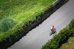 骑自行车者骑有充分的停止的一个登山车沿沿绿色种植园的一条柏油路 穿戴在天鹅绒c 免版税图库摄影