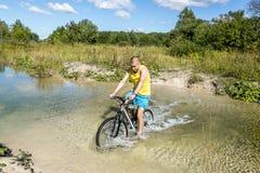 骑自行车者骑横跨河的一辆自行车在浅滩 库存照片