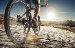 骑自行车者骑登山车的人脚细节在乡下公路的室外足迹 免版税库存图片