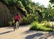 骑自行车者骑马在乡下公路的登山车 库存图片