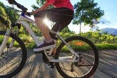 骑自行车者骑马在乡下公路的登山车 免版税库存照片