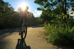 骑自行车者骑马在日出森林足迹的登山车 库存照片