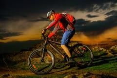 骑自行车者骑马在春天岩石足迹的登山车在美好的日落 极端体育和冒险概念 库存照片