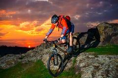 骑自行车者骑马登山车下来反弹岩石小山在美好的日落 极端体育和冒险概念 免版税图库摄影