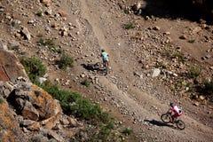 骑自行车者rasing二的沙漠山 免版税库存图片