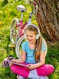 骑自行车观看在片剂个人计算机的女孩佩带的耳机 库存图片
