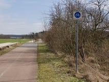 骑自行车轨道标志在一条农村路的边 免版税图库摄影