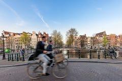 骑自行车通过城市街道在一美好的sumer天我的人们 库存照片