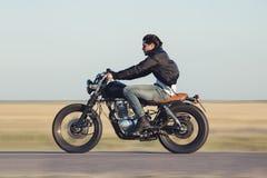 骑葡萄酒摩托车的年轻人 行动迷离的照相机摇摄 图库摄影