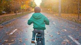 骑蓝色自行车的小男孩在城市公园在秋天 股票视频