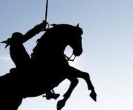 骑马和拿着剑的一个人的剪影 图库摄影