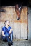 骑马女孩和马在槽枥 免版税库存照片