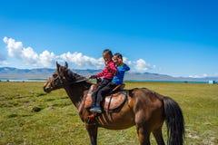 骑马的两个孩子 库存照片