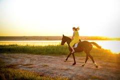 骑马的女孩在湖 免版税库存图片