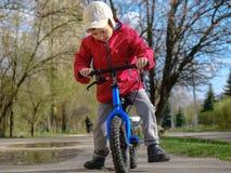 骑马的小孩男孩与他的第一辆自行车的在城市公园 五颜六色的衣裳的愉快的孩子 户外孩子的休闲 免版税库存照片
