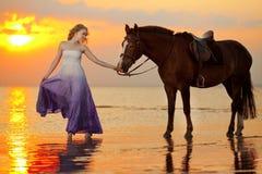 骑马的美丽的妇女在日落在海滩 年轻gir 免版税库存照片