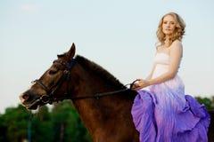 骑马的美丽的妇女在日落在海滩 年轻gir 库存照片