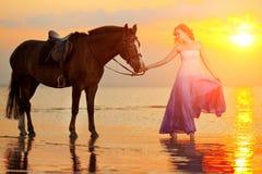 骑马的美丽的妇女在日落在海滩 年轻gir 库存图片