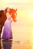 骑马的美丽的妇女在日落在海滩 年轻gir 免版税库存图片