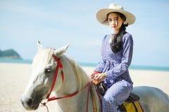 骑马的美女在海滩 免版税库存照片