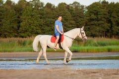 骑马的年轻人在日落在海滩 有的人hors 免版税库存照片