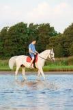 骑马的年轻人在日落在海滩 有的人hors 库存图片