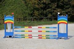 骑马障碍五颜六色的照片  马跳跃的事件竞争的空的领域 免版税库存照片