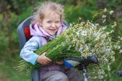 骑马画象在自行车儿童位子小白肤金发的女孩的有野生春黄菊花束的在手上 免版税库存照片