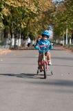 骑他小的自行车的愉快的男孩 免版税库存照片