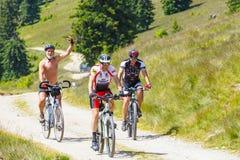 骑登山车的三个骑自行车者在晴天在山路,罗马尼亚 免版税图库摄影