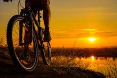 骑登山车的Enduro骑自行车者剪影在岩石足迹在日落 有效的生活方式概念 文本的空间 免版税库存图片