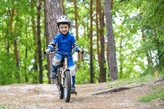 骑他的第一辆自行车的五颜六色的雨衣的愉快的滑稽的小孩男孩在森林活跃休闲的冷的天孩子的户外 免版税库存图片
