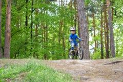 骑他的第一辆自行车的五颜六色的雨衣的愉快的滑稽的小孩男孩在森林活跃休闲的冷的天孩子的户外 库存照片