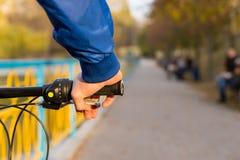 骑他的自行车的人通过公园 免版税库存图片