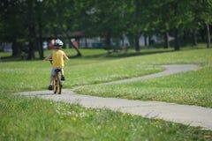 骑他的自行车的小男孩在扭转的窄路 免版税图库摄影