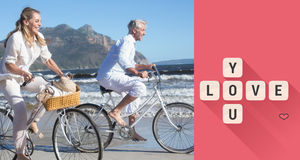 骑他们的自行车的微笑的夫妇的综合图象在海滩 库存照片