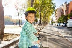 骑他的自行车的微笑的男孩在周期道路 库存图片