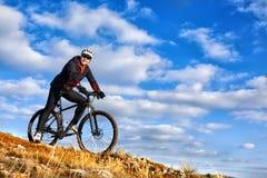 骑他的自行车的骑自行车者下来在山行迹 美丽的天空和云彩在背景 免版税图库摄影