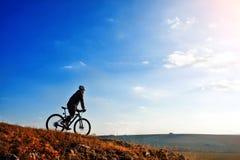 骑他的自行车的骑自行车者下来在山行迹 美丽的天空和云彩在背景 图库摄影