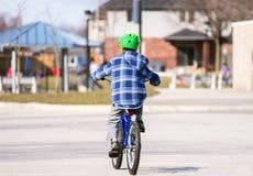 骑他的自行车的年轻男孩对下午的社区公园 库存照片