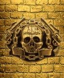 头骨、金黄枪和链子在wal金黄砖的背景  图库摄影