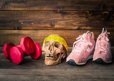 头骨和健身概念用锻炼设备在木 免版税库存图片