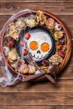 以头骨和新鲜的蕃茄的形式煎蛋 在万圣夜装饰的早餐 免版税图库摄影