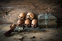 头骨和枪在木背景 免版税库存图片