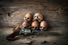 头骨和枪在木背景 免版税库存照片